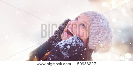 Winter young woman portrait. Beauty Joyful Model Girl touching her face skin and laughing, having fun in winter park. Beautiful young woman laughing outdoors. Enjoying nature, wintertime.