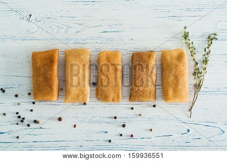 Stuffed pancakes on a light wooden background