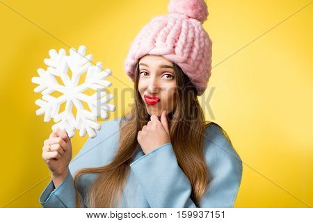 Thoughtful woman in colorful winter clothes holding a snowflake on the yellow background