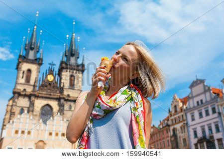 woman eating ice cream on a background of Tyn Cathedral, Prague, Czech Republic