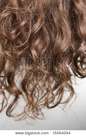 brown curly hair against grey background
