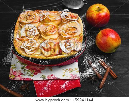 Fruit apple pie tartlet (cake). On top of the pie cake in the shape of apples rose flowers. Fresh fruit apples for pie cake. The dark black wooden background.