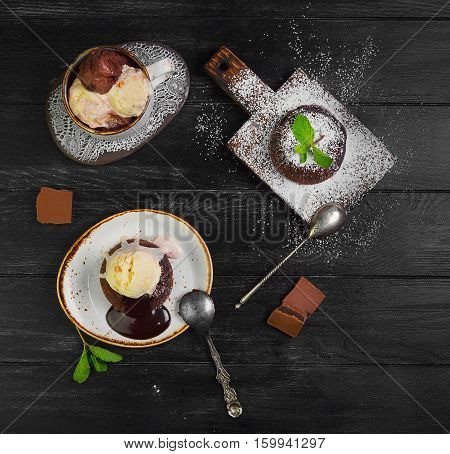 Chocolate lava cake (Molten) with ice cream on plate. Balls of ice cream in cup. Chocolate lava cake (Molten) with mint on board. Pieces of chocolate. Dark black wooden background. Top view blank space.