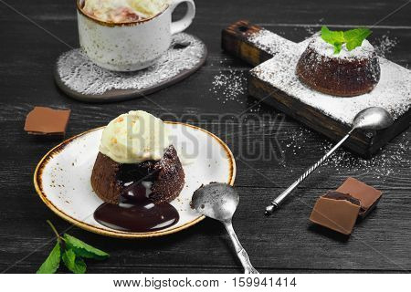 Chocolate lava cake (Molten) with ice cream on plate. Balls of ice cream in cup. Chocolate lava cake (Molten) with mint on board. Pieces of chocolate. Dark black wooden background.