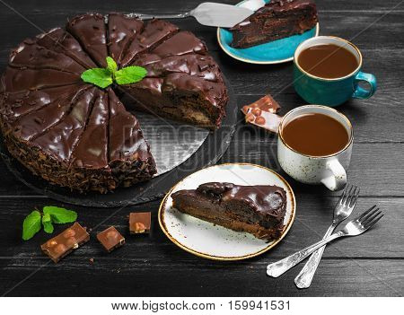 Big chocolate cake torte. Ingredients for chocolate cake torte mint chocolate chips. Slices chocolate cake on saucer. Drink hot chocolate cocoa (coffee) in cups. Black wooden background.