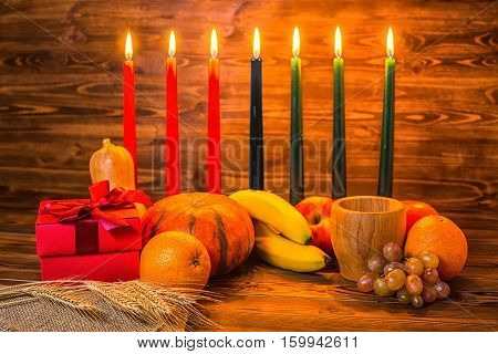 Kwanzaa Holiday Concept With Traditional Lit Candles, Gift Box, Pumpkins, Ears Of Wheat, Grapes, Ora