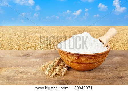 wheat flour in ceramic bowl. Ears of wheat and wheat flour in bowl on table with field of wheat on the background. Golden wheat field and blue sky. Photo with copy space area for a text