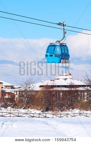 Ski resort Bansko, Bulgaria panorama with cable car ski lift cabin, snow mountains and houses
