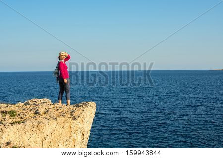Woman In A Straw Hat Standing On The Rocky Shore