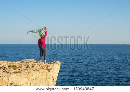 Woman Standing On Rocky Shore, With Scarf Fluttering In Wind
