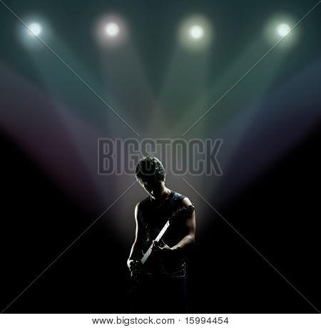 joven músico tocando la guitarra en el escenario