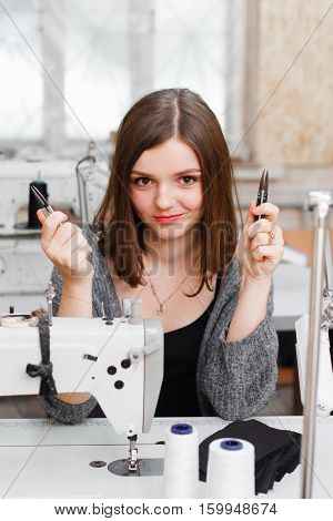 Young smiling seamstress posing with scissors. Attractive female tailor sitting at sewing machine and showing her work nippers at camera. Garment industry, fashion designer concept