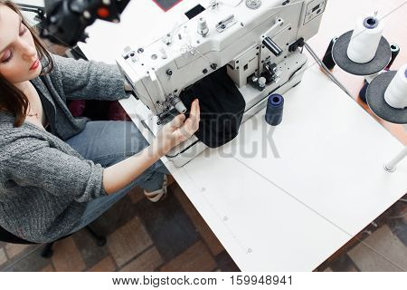 Top view on tailor working with sewing machine, free space. Young attractive seamstress stitching dark fabric. Garment industry, designer atelier, clothes making concept