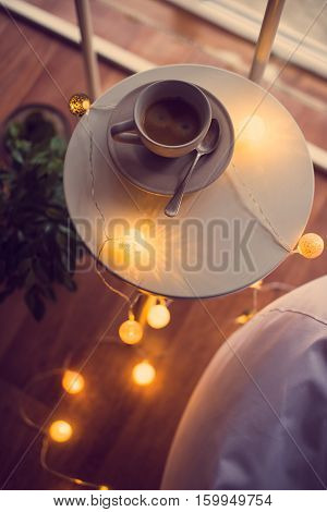 Cup of coffee and warm Christmas lights on a table, cozy moody room interior