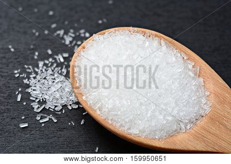 mono-sodium glutamate in wooden spoon and on black wooden table