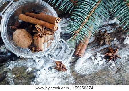 Christmas spices still life with cinnamon sticks and star anise on a wooden background with fir tree and snow. Anise and cinnamon for Christmas. Christmas spices concept. Selective focus.