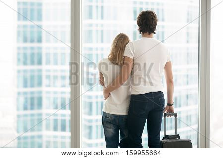 Rear view of attractive young couple in modern apartment looking in full length window at big city scenery, holding suitcase, leaving hometown, or arriving to new place, travelling together. Indoors