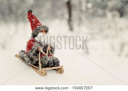 Toy Santa Claus On A Sledge In A Snowy Forest