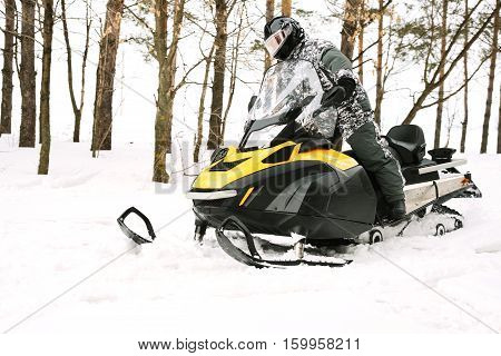 The sportsman on a snowmobile. Recreation concept on nature in winter and New Year holidays. Winter sports. poster