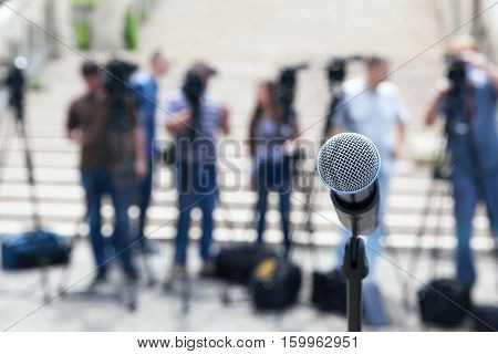 Microphone in focus against blurred camera operators and journalists. Press conference.