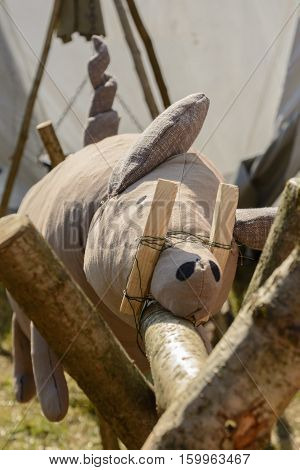 Decorative stuffed suckling pig on wooden grill - close-up