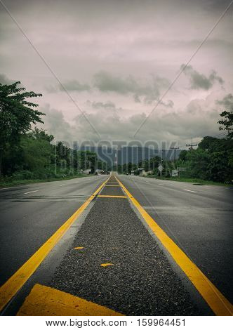 Long country road with yellow lines down the center of the road with cloudy sky