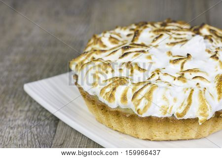 Small lemon pie on a white plate on a wooden table.