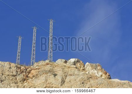 Three high voltage towers on a rocky mountain with a blue sky.