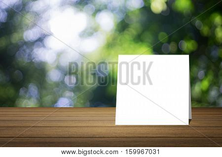White Card Put On Wooden Desk Or Wooden Floor On Blurred Green Tree Nature Background.use For Presen