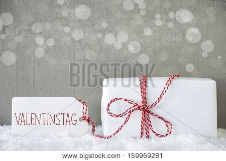 One Christmas Present On Snow. Cement Wall As Background With Bokeh. Modern And Urban Style. Card For Birthday Or Seasons Greetings. Label With German Text Valentinstag Means Valentines Day