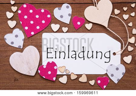 One Label With German Text Einladung Means Invitation. Flat Lay View With Wooden Vintage Background. Pink Wooden And Paper Hearts.