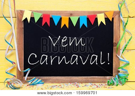 Blackboard With Spanish Text Vem Carnaval Means Happy Carnival. Party Decoration Like Streamer And Confetti. Yellow Wooden Background. Greeting Card For Celebrations