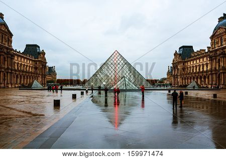 PARIS FRANCE - NOVEMBER 17 2014: Louvre pyramid of museum with cloudy sky during the rainy day in Paris France. It is one of the world's largest museums and a historic monument popular landmark