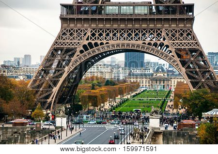 Paris France. Close view of famous Eiffel Tower and Champ de Mars with people and cars during the cloudy day in Paris. It most-visited paid monument in the world even in autumn it's full of tourists
