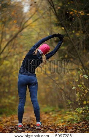 Young blonde on stretching exercises in autumn park