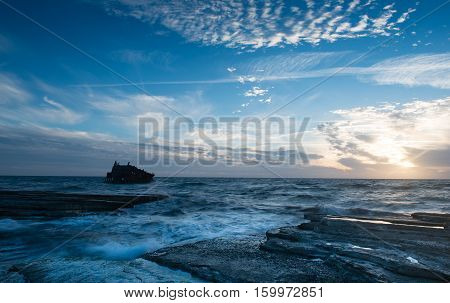 Shipwreck of an abandoned ship on a rocky coast at Akrotiri Beach in Cyprus