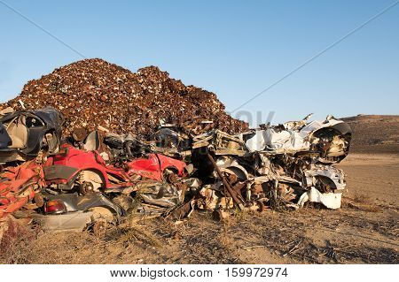 Pile of various scrap cars and other metals on a field ready for the recycling industry.