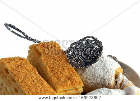 Homemade pastries on a brown ceramic plate with kitchen serving tongs