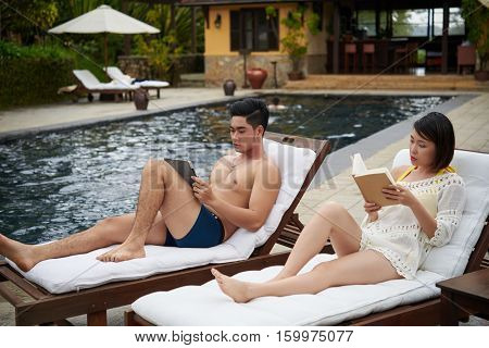 Young Asian man reading e-book and his girlfriend reading book at the pool