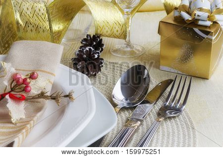 Beautiful decoration for festive dinner. Christmas table settings in gold tone: cutlery with napkin on linen tablecloth. Winter holiday background. Merry Christmas or Happy New Year concept.
