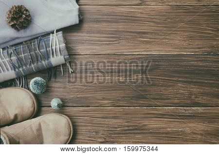 winter knitted clothes . Cashmere sweater ugg boots wool square scarf and mittens little Christmas tree and natural fir cone on wooden background. Concept for Winter and Christmas. Copy space.