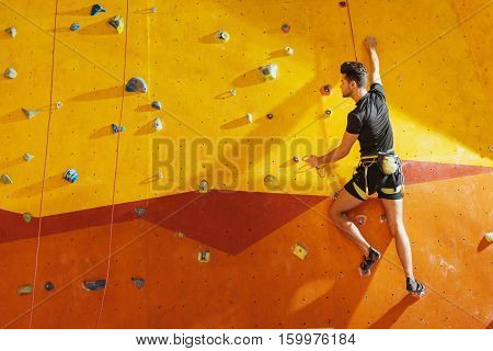 Extreme way of life. Fearless handsome young man climbing up the wall while spending time in climbing gym and using equipment.