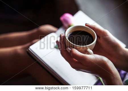 Girl reading book and drinking coffee beautiful rose. Morning hobbies flowers study