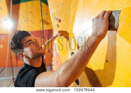 One way or another. Active handsome young man training in climbing gym while climbing up the wall and using insurance ropes.