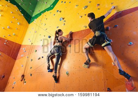 Together funnier. Delighted active young man and woman climbing up the wall while training and spending time together in climbing gym.