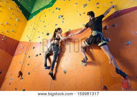 Fun together. Delighted athletic young man and woman climbing up the wall while training and holding hands in climbing gym.