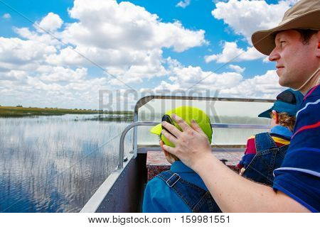 Little kid boy and father making air boat tour in Florida wetland swamp at Everglades National Park in USA. Family, dad and child discovering wild nature and animals. Family having fun.