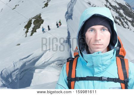 Climber man stands in winter mountains, Snowboarders walking uphill for freeride in the background.