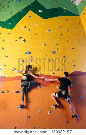 Full of happiness. Amused athletic young couple climbing up the wall together while training and holding hands in climbing gym.