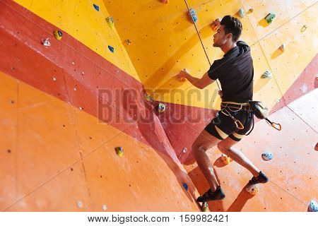 Pleasant times. Handsome young delighted man training hard in climbing gym while using equipment and climbing up the wall.
